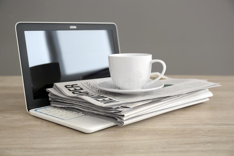 Mucchio dei giornali, del computer portatile e della tazza di caffè sulla tavola di legno fotografie stock libere da diritti