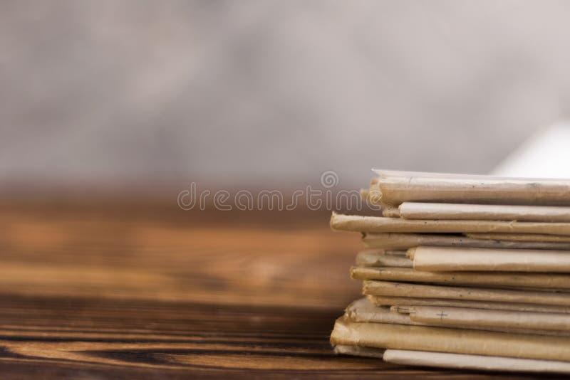 Mucchio dei giornali impilati sulla vecchia tavola di legno marrone su fondo del muro di cemento fotografie stock libere da diritti