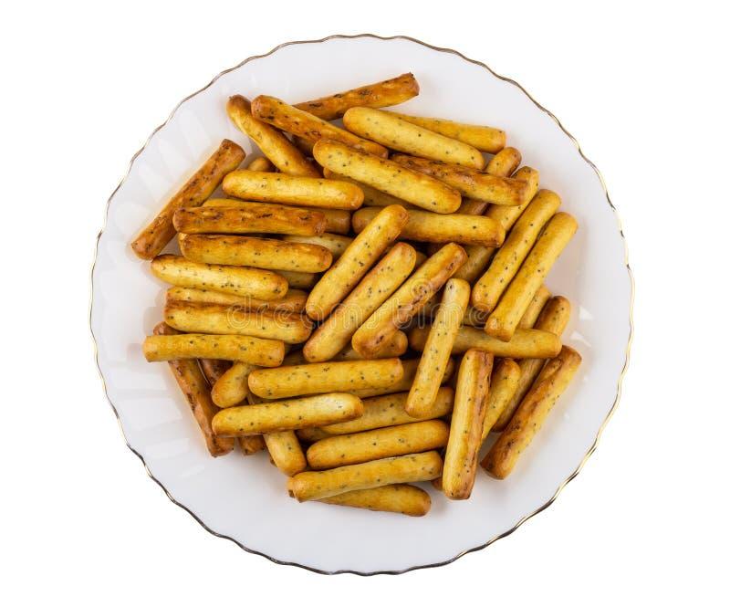 Mucchio dei grissini con il papavero in piatto isolato su bianco Vista superiore fotografie stock libere da diritti