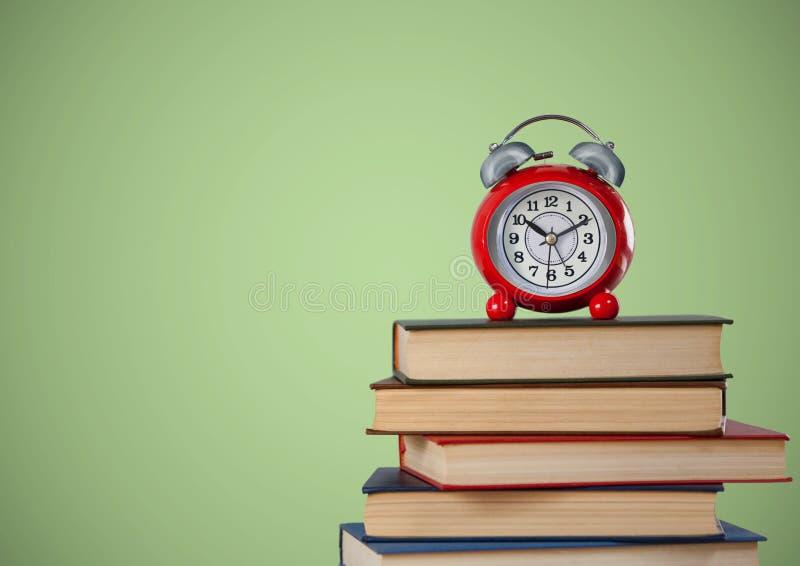 Mucchio dei libri e dell'orologio contro fondo verde fotografia stock libera da diritti