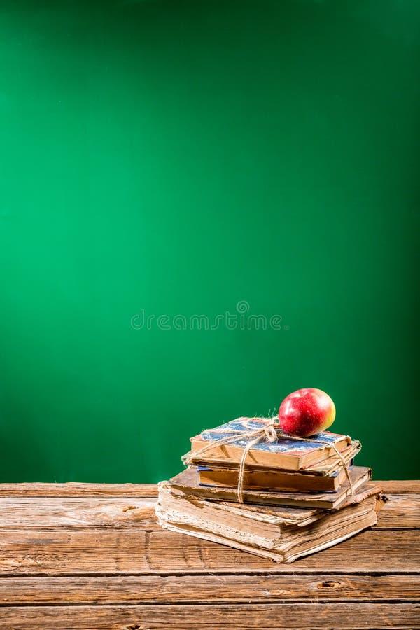 Mucchio dei libri e della mela al fondo della lavagna immagine stock libera da diritti