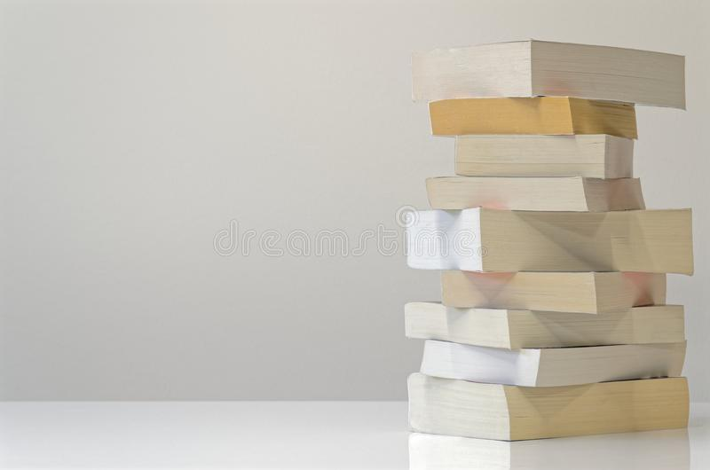 Mucchio dei libri sulla tavola bianca e sui precedenti grigio chiaro immagini stock