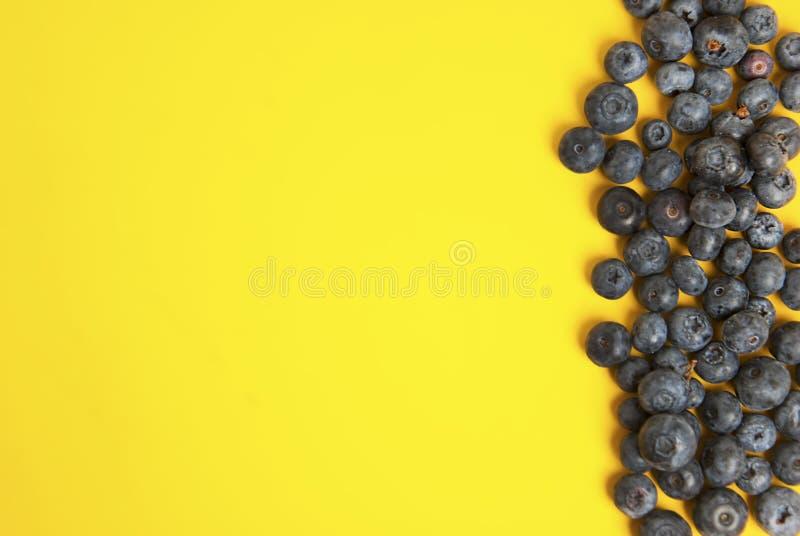 Mucchio dei mirtilli isolati su fondo variopinto giallo Bacca della frutta di vibrazione di estate con lo spazio della copia Ingr immagine stock libera da diritti