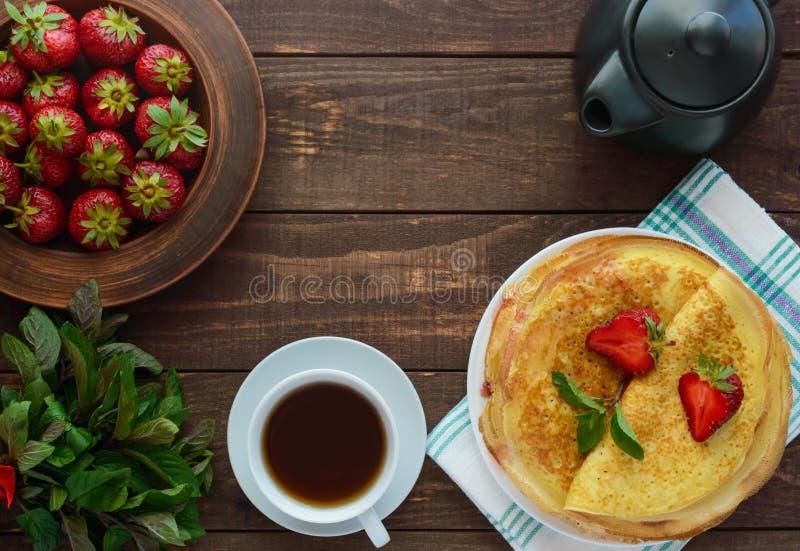 Mucchio dei pancake dorati con le fragole e l'inceppamento di fragola, ramoscello decorativo della menta fotografie stock