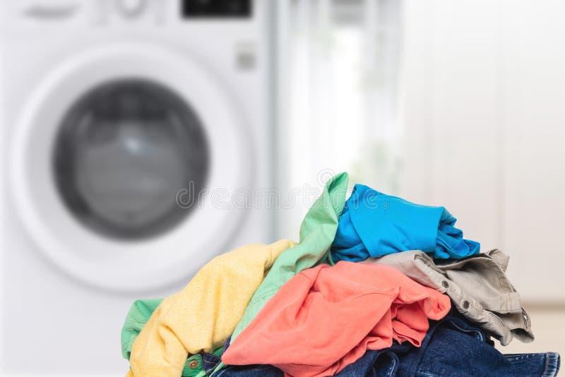Mucchio dei vestiti Pila di vestiti sporchi variopinti pronti per la lavanderia contro fondo vago luminoso fotografia stock libera da diritti