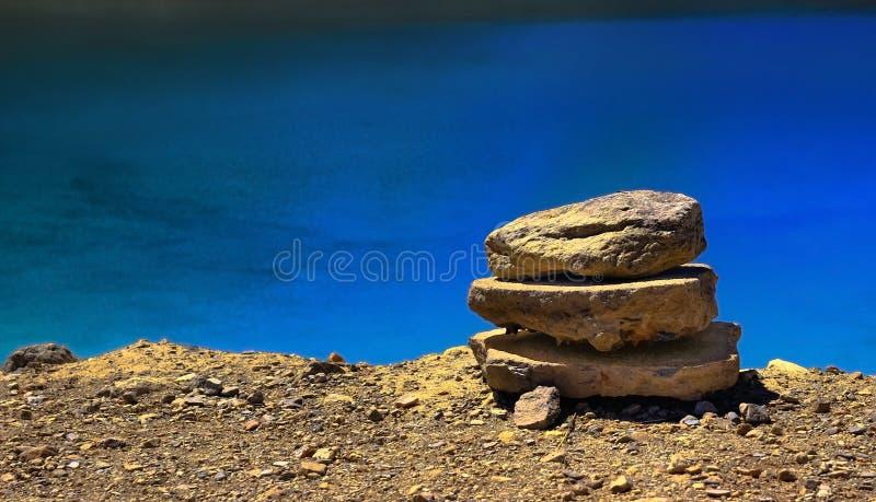 Mucchio del ciottolo impilato sulla riva del lago con acque ancora blu nei precedenti fotografia stock