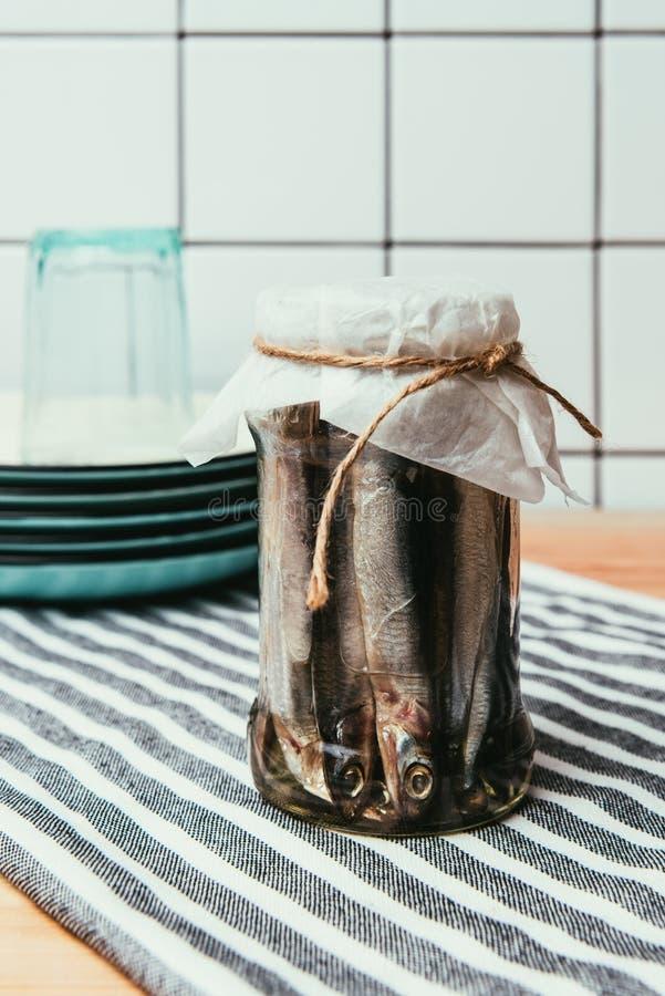 Mucchio del pesce salato in barattolo avvolto da corda sull'asciugamano con i piatti immagine stock libera da diritti