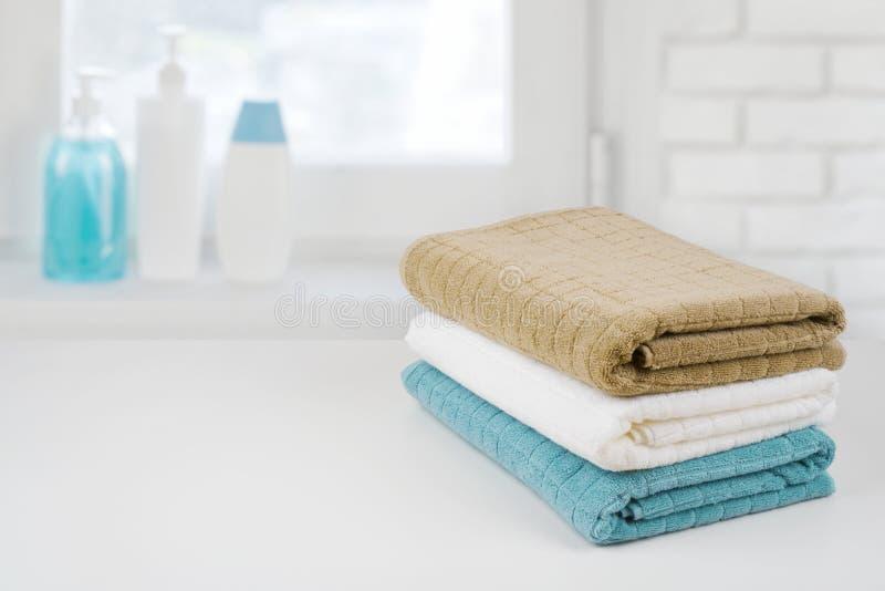 Mucchio dell'asciugamano di bagno su legno sopra il fondo defocused di davanzale del bagno fotografia stock