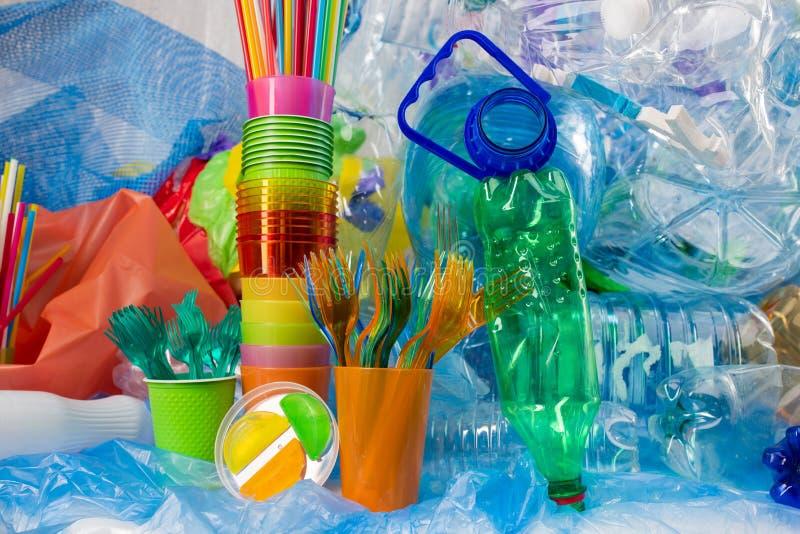 Mucchio della coltelleria di plastica disposto fra le bottiglie utilizzate e le paglie variopinte fotografie stock