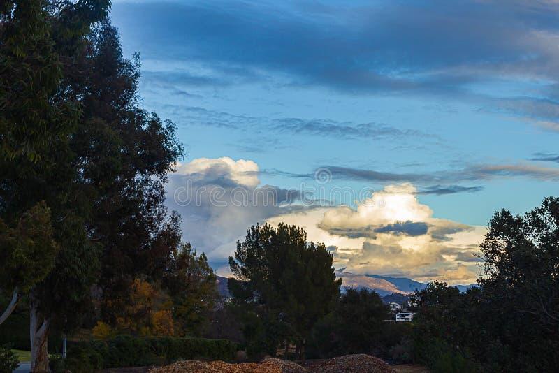 Mucchio della composta con la vista del pendio di collina della vista panoramica delle nuvole di tramonto immagine stock