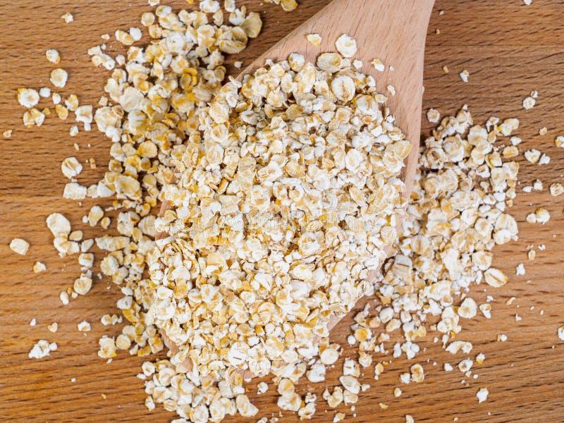 Mucchio della farina d'avena in cucchiaio di legno su fondo di legno, vista superiore immagine stock