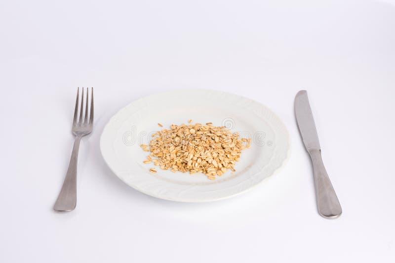 Mucchio della farina d'avena su un piatto isolato su bianco fotografia stock libera da diritti