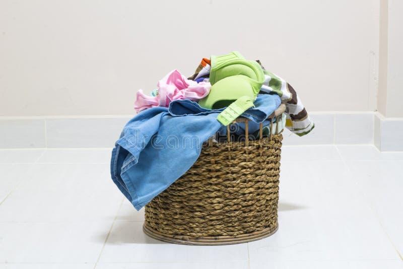 Mucchio della lavanderia sporca in un canestro di lavaggio su un fondo bianco fotografie stock
