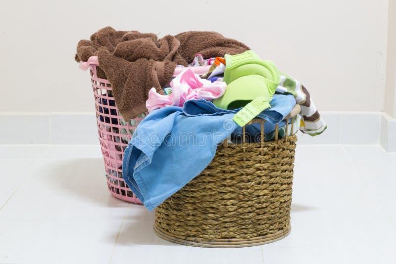 Mucchio della lavanderia sporca in un canestro di lavaggio su un fondo bianco fotografia stock