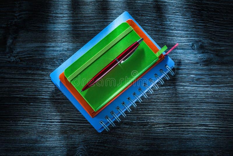 Mucchio della penna dei taccuini sul bordo di legno d'annata fotografia stock libera da diritti