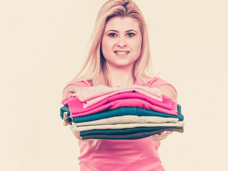 Mucchio della tenuta della donna dei vestiti piegati fotografia stock