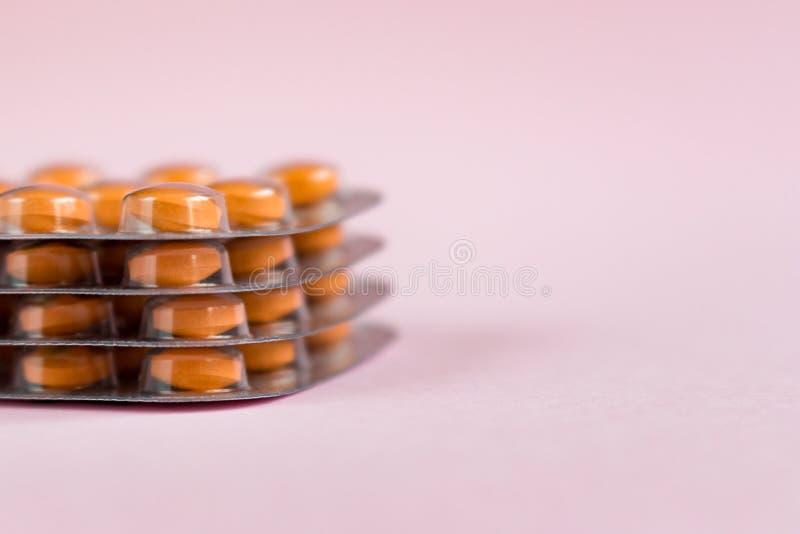 Mucchio delle bolle con le pillole della medicina su fondo rosa Pila di compresse, capsule fotografie stock libere da diritti
