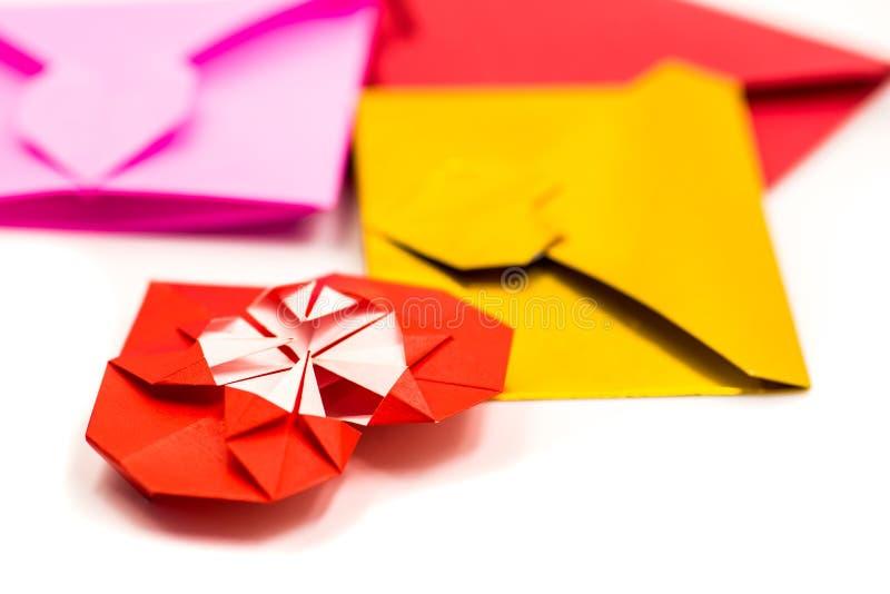 Mucchio delle buste di carta di origami variopinti e del cuore rosso isolati su bianco immagine stock libera da diritti