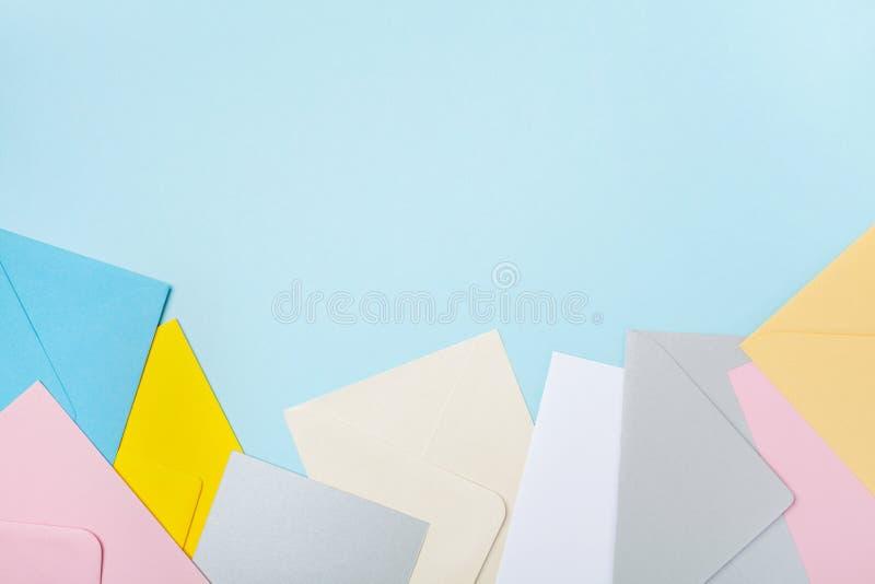 Mucchio delle buste variopinte sulla vista da tavolino di lavoro blu Modello per la posta di affari, il blogging e la corrisponde fotografie stock libere da diritti