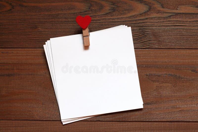 Mucchio delle carte con un clothespeg di legno con cuore rosso su una tavola di legno immagini stock