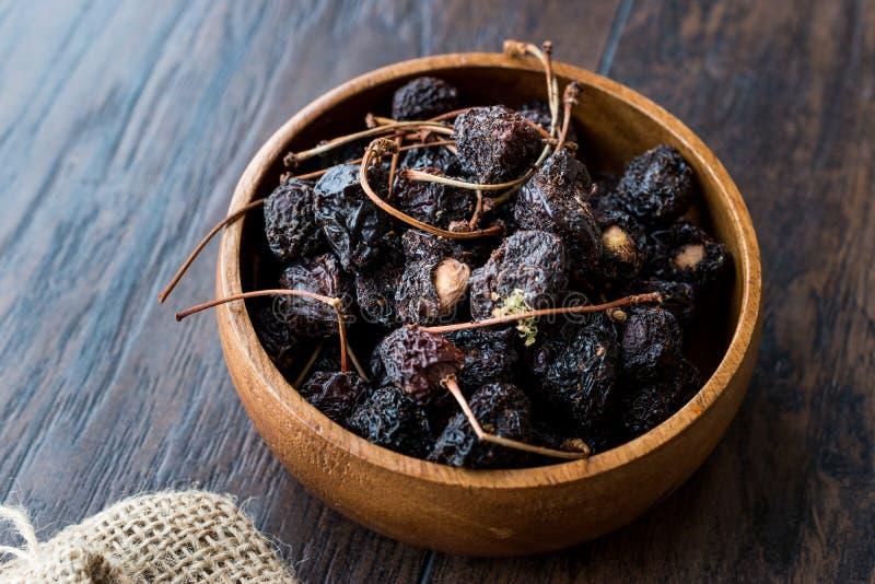 Mucchio delle ciliege secche in ciotola di legno pronta da mangiare immagine stock