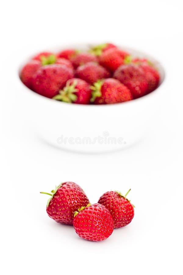 Mucchio delle fragole fresche davanti alla ciotola bianca in pieno di fragole fotografia stock