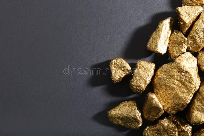 Mucchio delle pepite di oro su fondo scuro, disposizione piana immagini stock