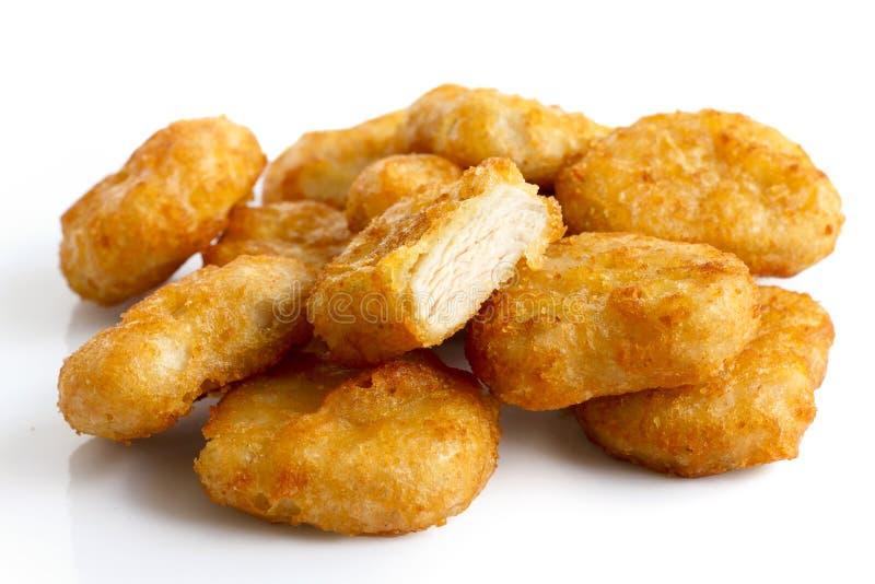 Mucchio delle pepite di pollo avariate fritte in grasso bollente dorate isolate su w immagine stock