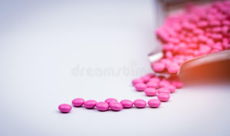 Mucchio delle pillole rotonde rosa delle compresse rivestite dello zucchero sul vassoio della droga con lo spazio della copia fotografia stock