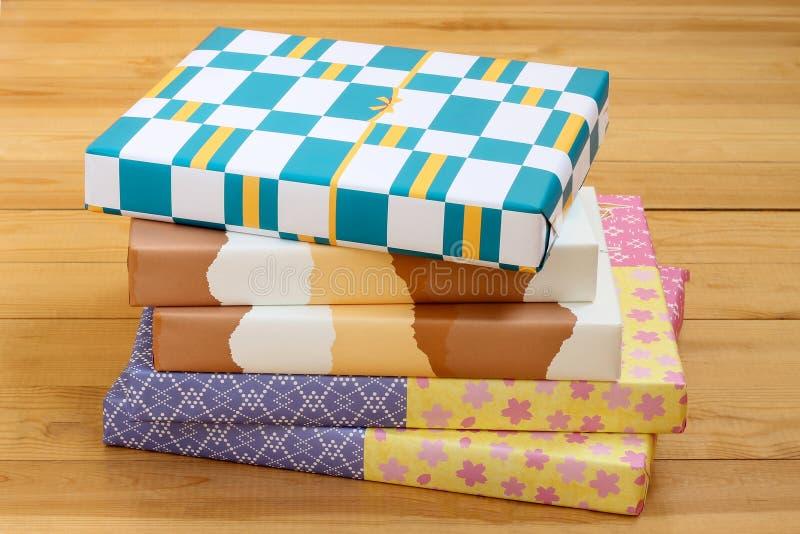 Mucchio delle scatole dei colori del cartone su fondo di legno fotografia stock