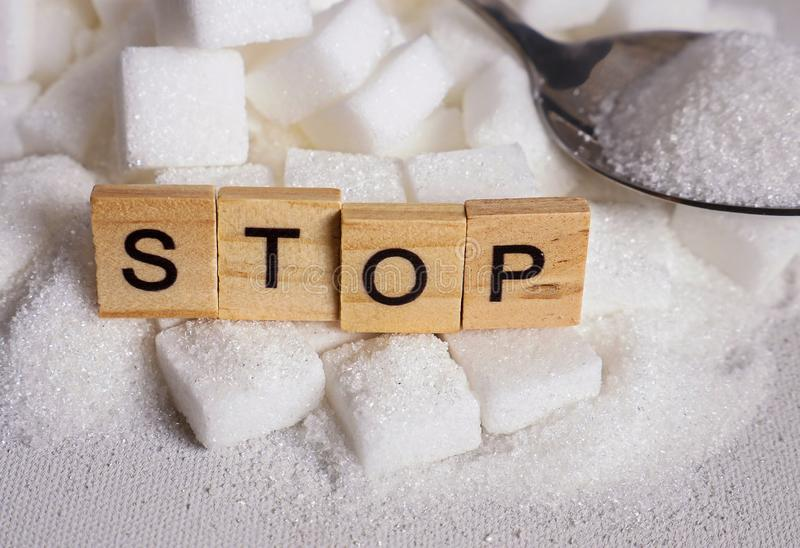 Mucchio di H dei cubi dello zucchero bianco e fermare parola nei caratteri in grassetto come consigliano su abuso non sano in ecc immagini stock