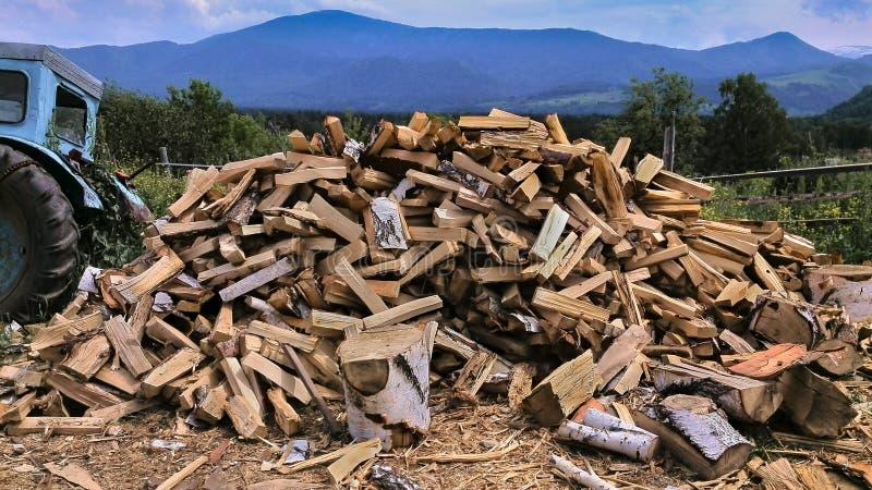 Mucchio di legna da ardere tagliata, vecchio trattore nel paesino di montagna, il Kazakistan orientale, un giorno di estate fotografie stock libere da diritti