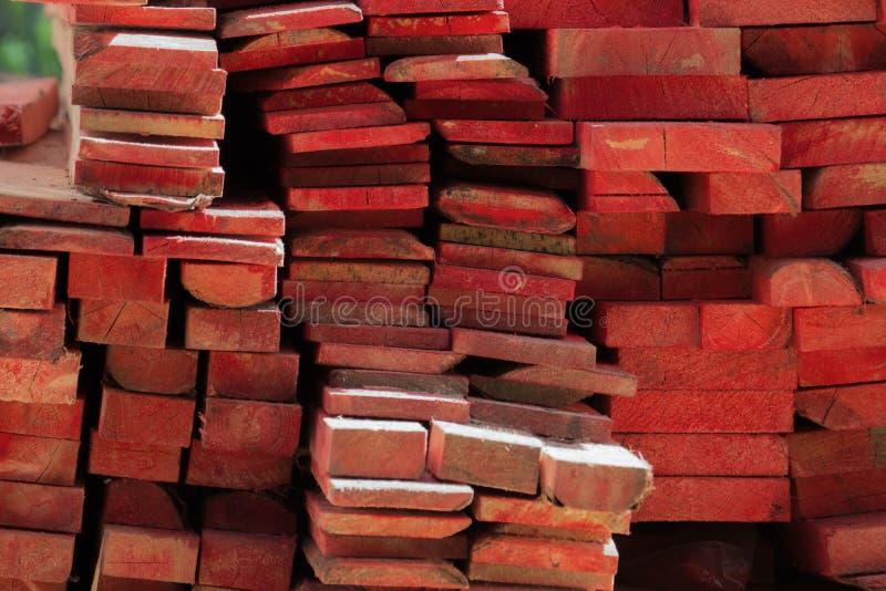 Mucchio di legno impilato dipinto delle barre di colore rosso Materiali da costruzione immagine stock