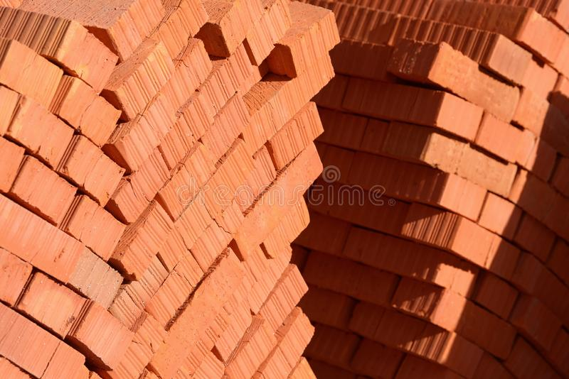 Mucchio di nuovi mattoni rossi impilati Blocchetti del mattone dell'argilla pronti per costruzione fotografia stock