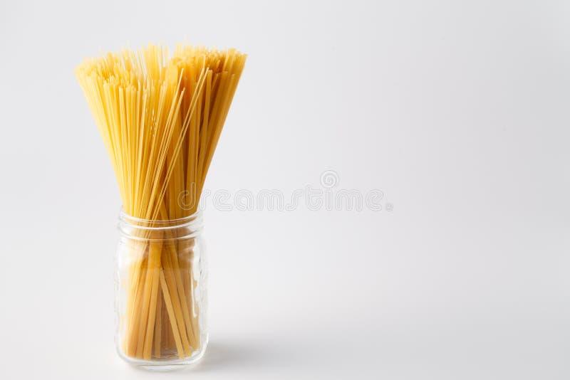Mucchio di pasta italiana cruda in barattolo di vetro su bianco con la copia s immagine stock libera da diritti