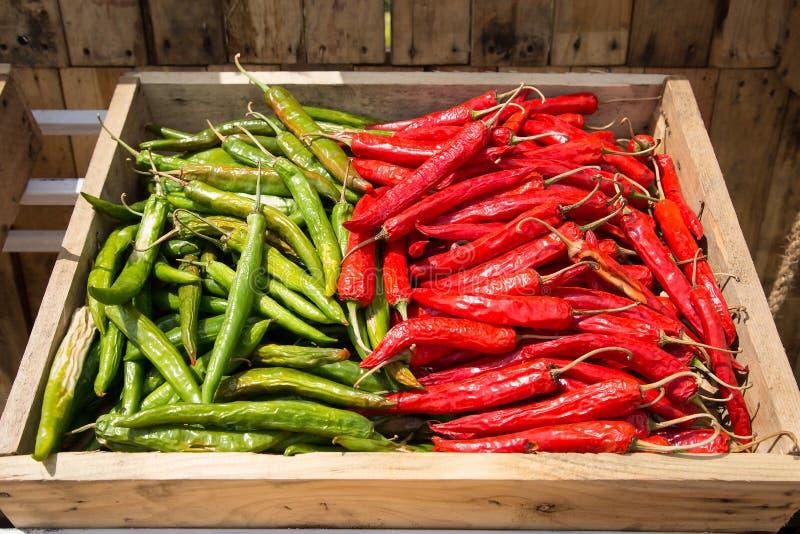 Mucchio di peperoncino, di rosso caldo e di peperoni verdi sulla BO di legno immagini stock