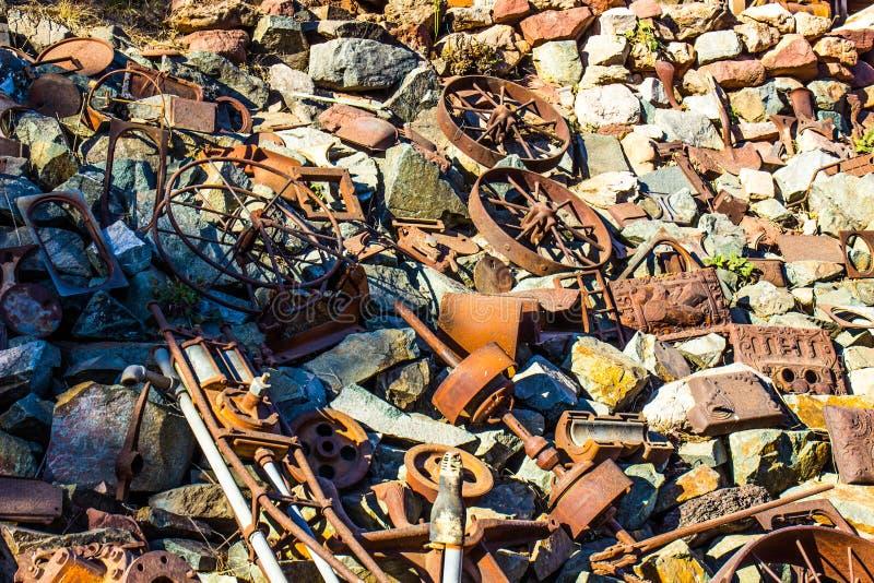 Mucchio di Rusty Iron Debris And Wheels d'annata nell'iarda di ciarpame immagine stock