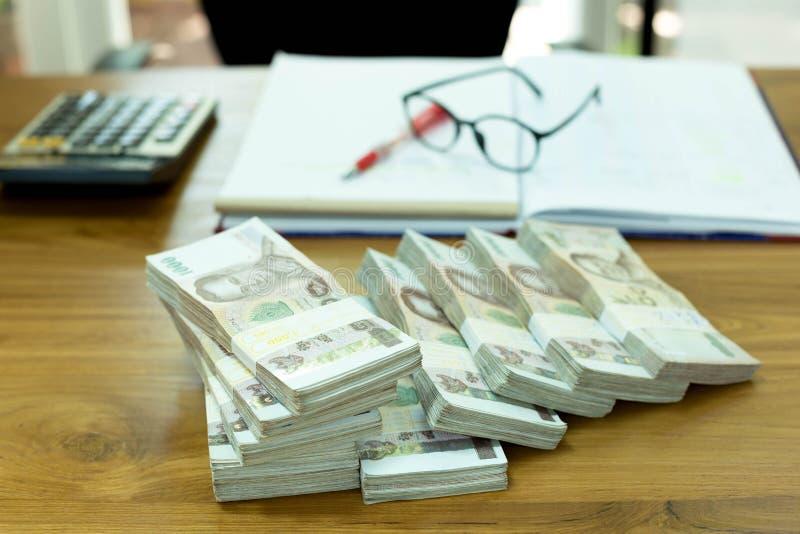 Mucchio di soldi tailandesi con i vetri ed il taccuino sulla tavola di legno fotografie stock