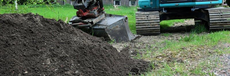 Mucchio di suolo, della pala e delle piste compatte dell'escavatore immagine stock libera da diritti