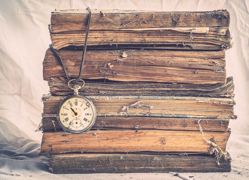 Mucchio di vecchi libri polverosi con l'orologio da tasca rotto su bianco sporco immagine stock