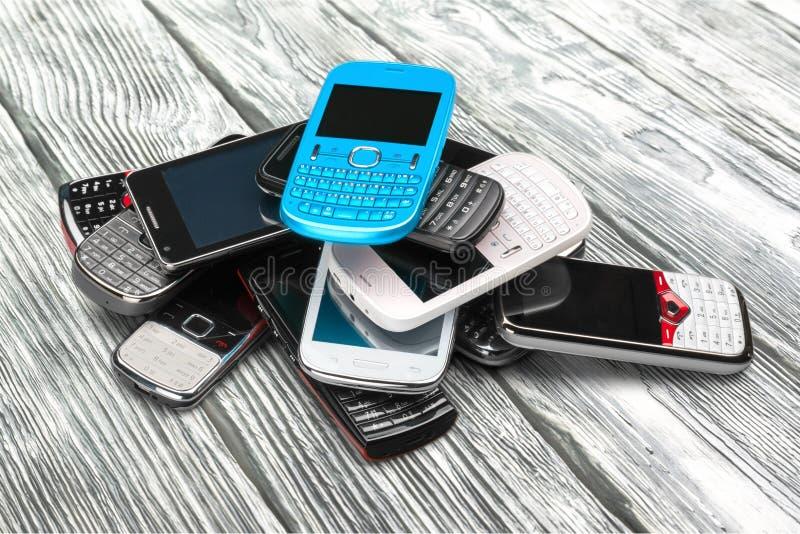 Mucchio di vecchi smartphones su fondo di legno fotografie stock libere da diritti