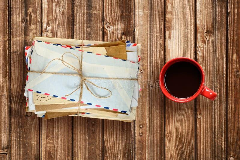 Mucchio di vecchie buste e tazza di caffè sulla tavola di legno fotografia stock libera da diritti