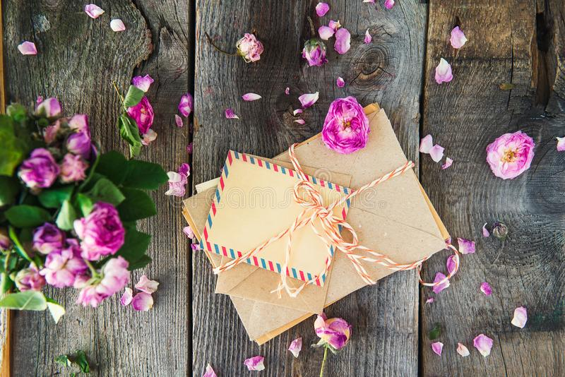 Mucchio di vista superiore di vecchie lettere in buste della carta del mestiere, cartolina d'auguri in bianco e fiori rosa appass immagini stock