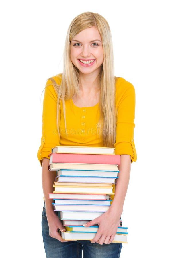 Mucchio felice della tenuta della ragazza dello studente dei libri immagine stock libera da diritti