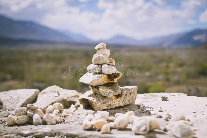 Mucchio impilato delle pietre o delle rocce di zen con la bella montagna fotografia stock libera da diritti