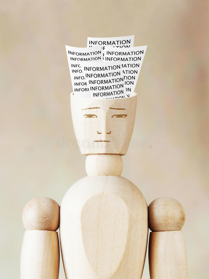 Much various information into the human head. Abstract image with wooden puppet royalty free stock photography