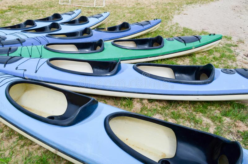 Mucha canoa azul y verde kayaks con las partes delanteras de las narices para los deportes acuáticos, nadando mentira en la playa imagenes de archivo