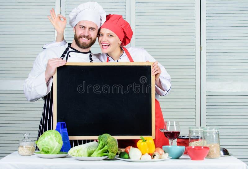 Mucha clase de cocina de la diversión Cocinero principal y cocinero de la preparación que gesticula la muestra aceptable en el ta fotografía de archivo