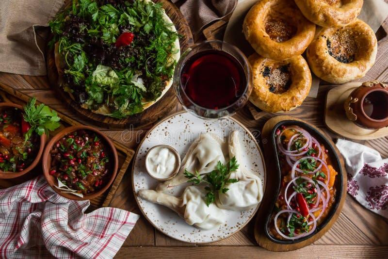 Mucha comida en la tabla de madera Cocina georgiana Visión superior Endecha plana Khinkali y platos georgianos fotos de archivo