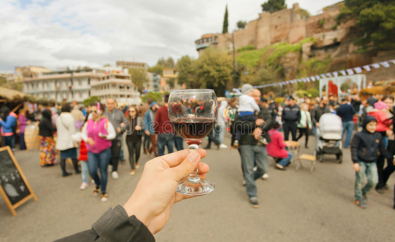 Mucha gente con las familias que caminan las calles de la celebración con el vino durante el festival Tbilisoba País de Tbilisi,  fotografía de archivo libre de regalías